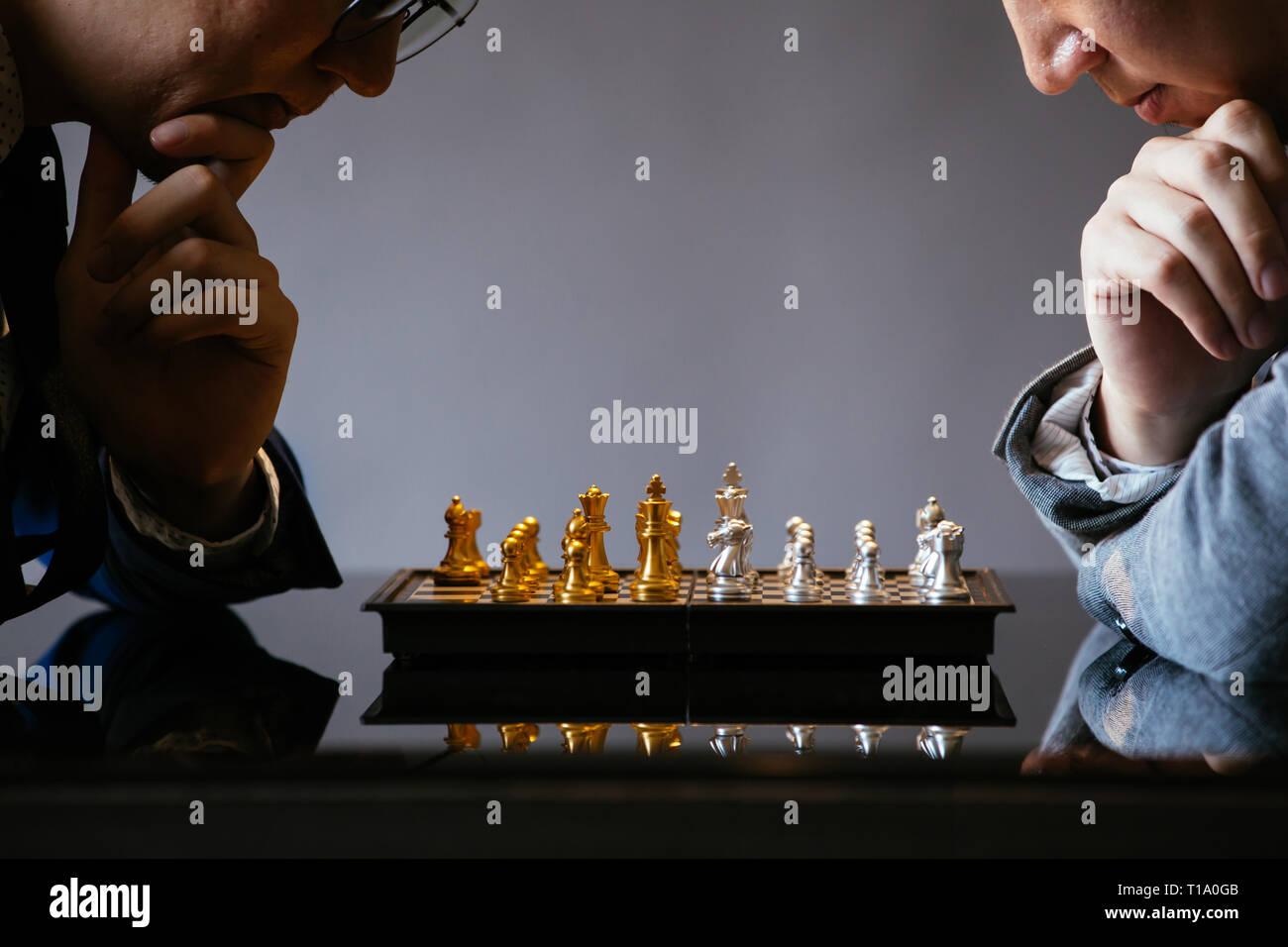 Dos empresarios unrecogniazble pensando se mueve mientras está jugando al ajedrez contra el fondo gris Foto de stock