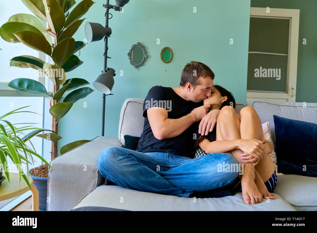 Pareja besándose en el sofá en casa Foto & Imagen De Stock ...