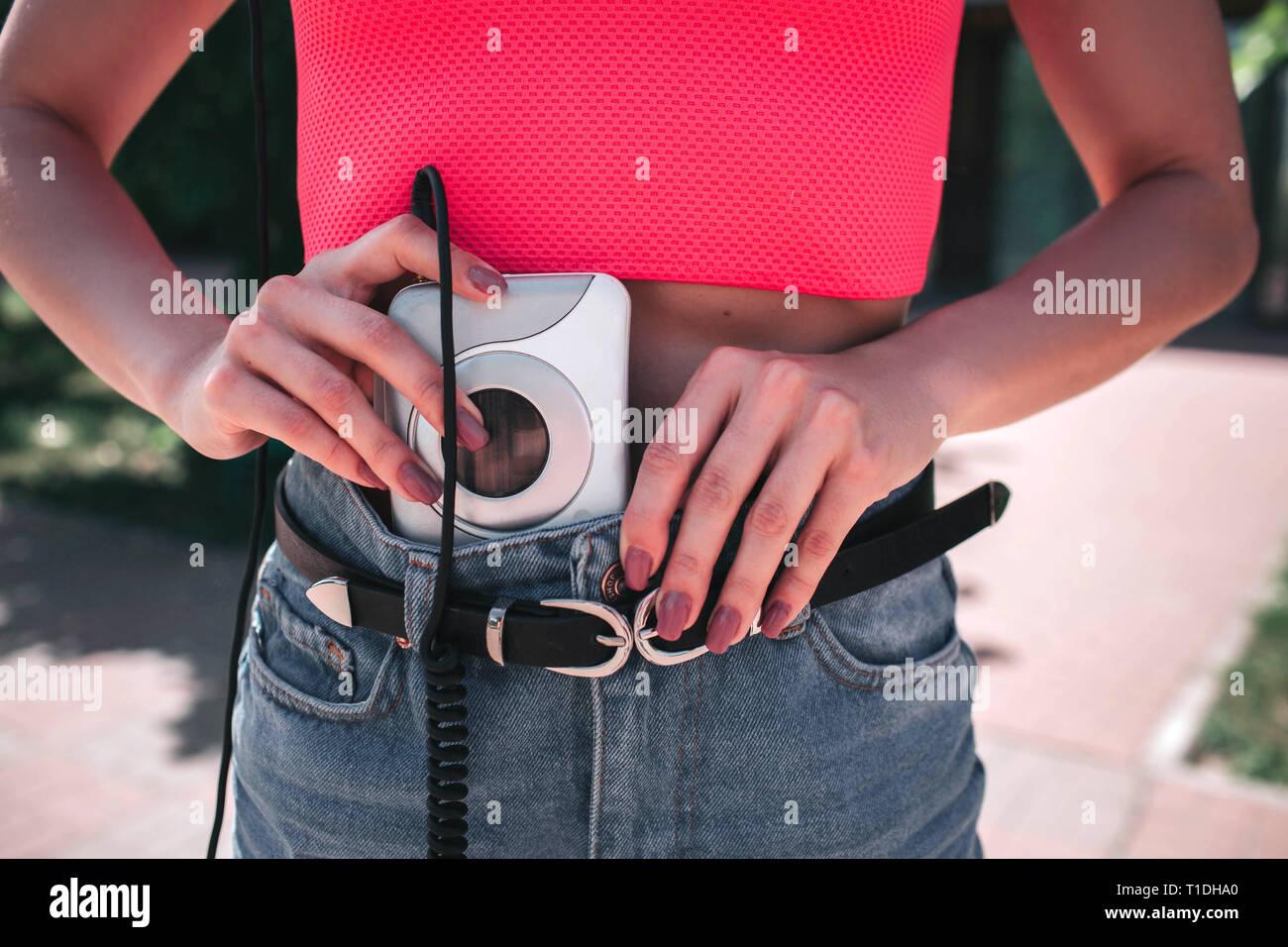 Una imagen de chica poniendo music player en pantalones vaqueros. Es blanca y reproductor de música a los auriculares conectados por cable. Foto de stock