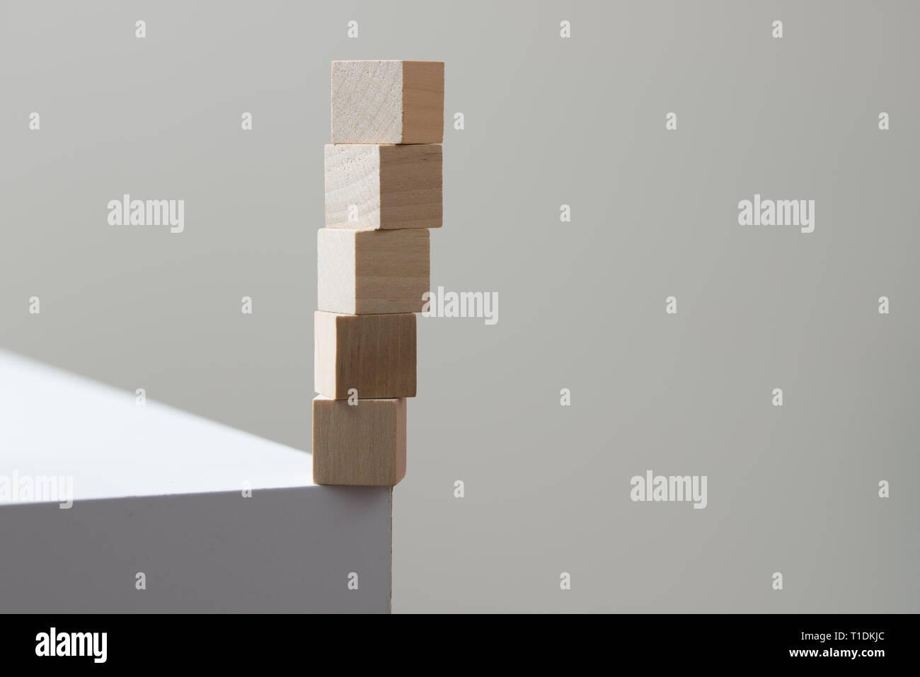 Cubos de madera en equilibrio en el borde de la mesa para el concepto de riesgo Foto de stock