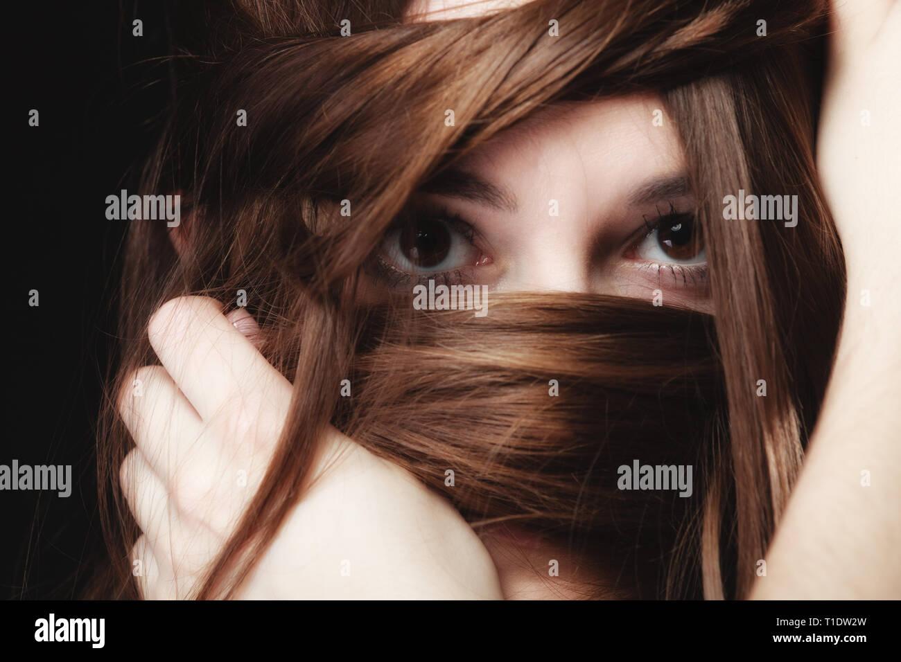 Soledad, estrés y ansiedad mujeres concepto. Closeup retrato Mujer hermosa morenaza, jovencita que cubren cara por largos pelos marrones sobre negro Foto de stock