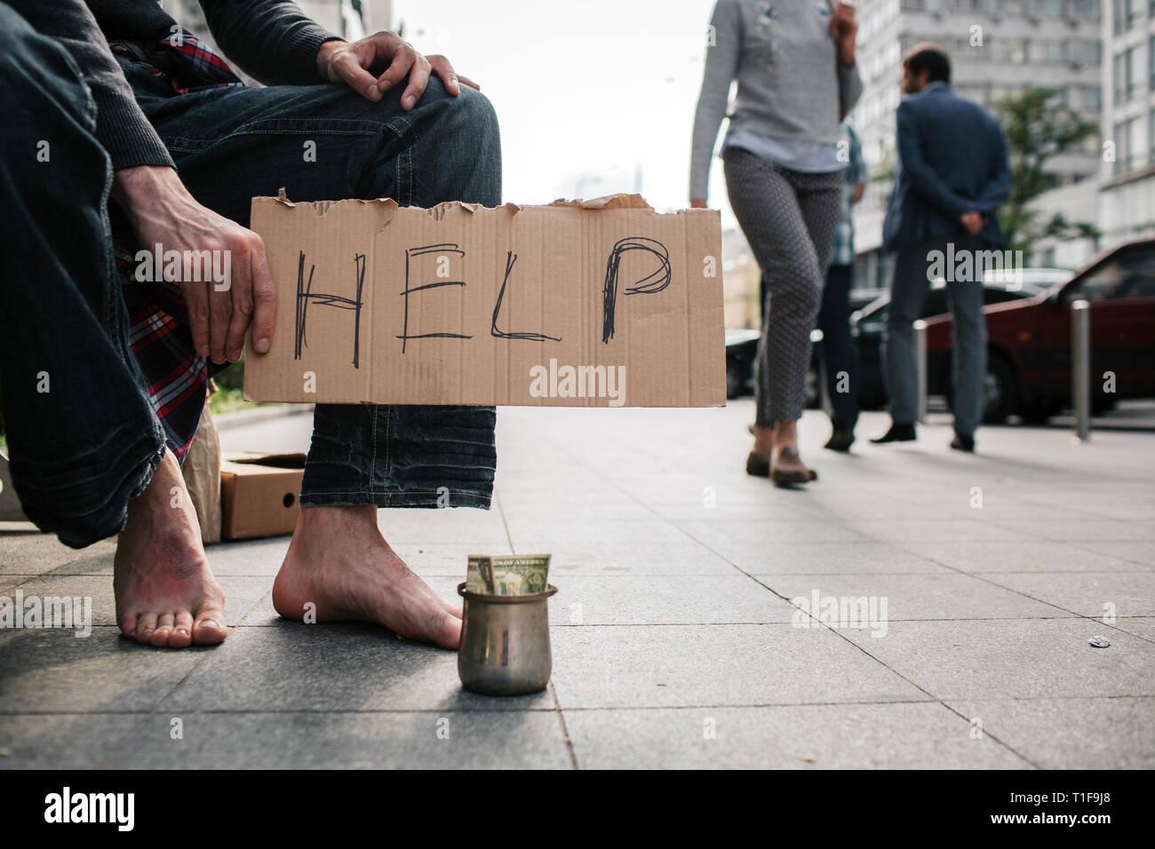 Una imagen del hombre sin piernas zapatos de pie en el suelo de hormigón. Existe una copa metálica con dinero en ella. Guy está sosteniendo un cartón que dice Foto de stock
