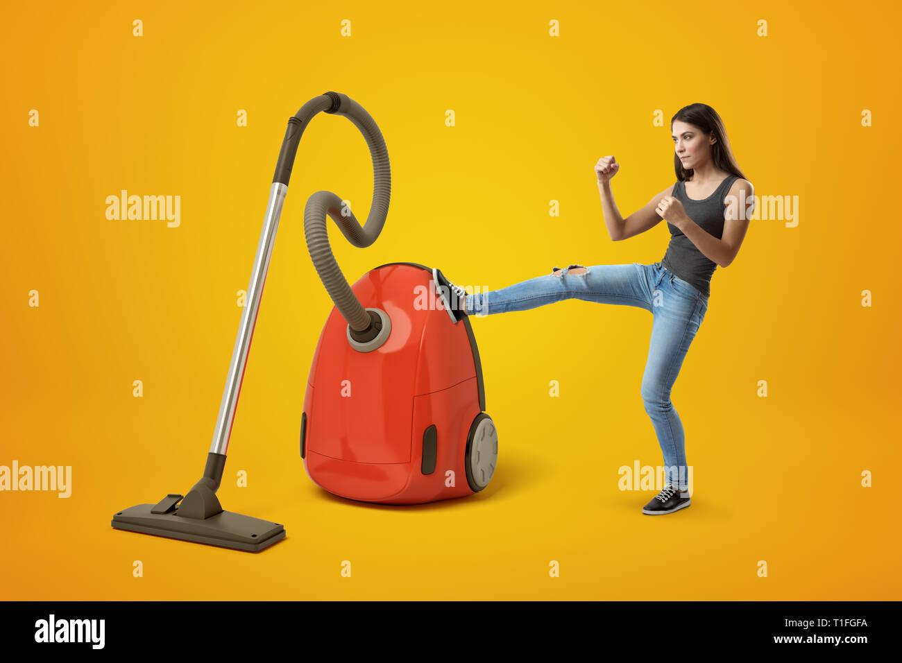Joven en superior gris y jeans, los puños clenched y elevada, aspirador grande rojo patadas con la pierna derecha sobre fondo amarillo. Imagen De Stock