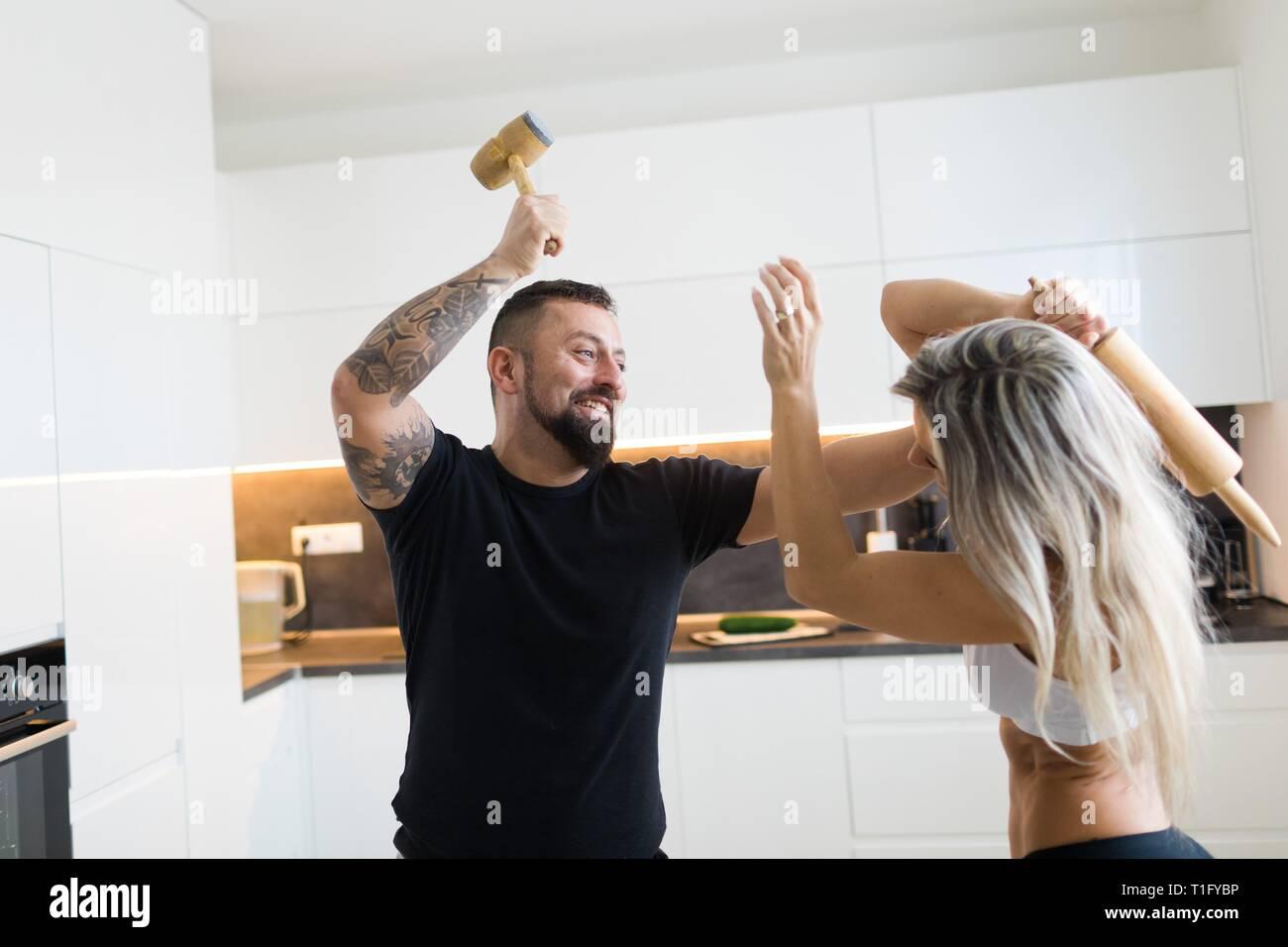 El esposo y la esposa de enfrentamiento en cocina con rodillo de masa y carne Mallet. El lado negativo de la relación entre el hombre y la mujer. Imagen De Stock