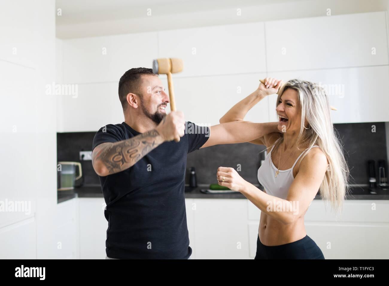 El esposo y la esposa de enfrentamiento en cocina con rodillo de masa y carne Mallet. Divertirse juntos. Imagen De Stock