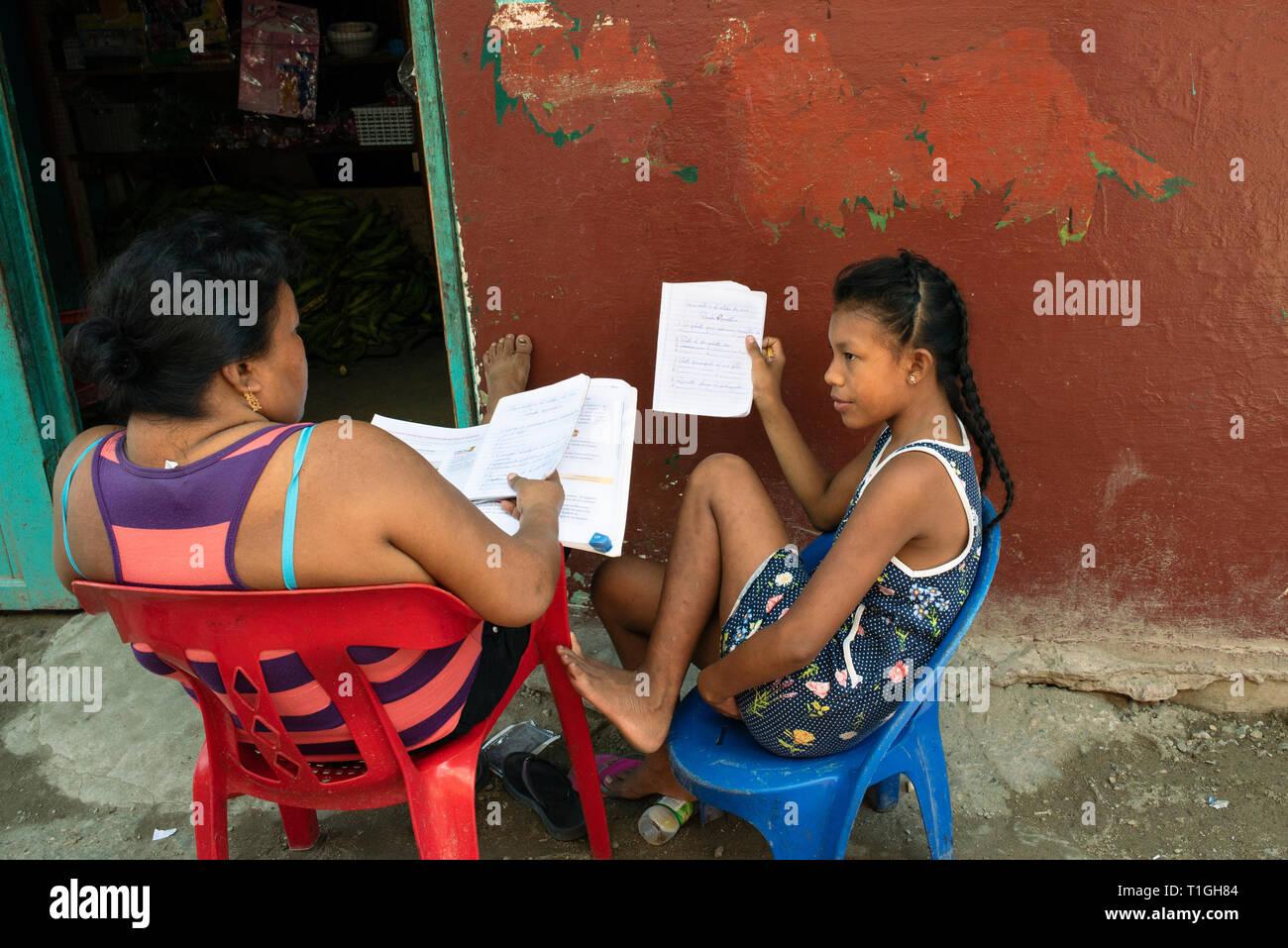 Niña y madre comprobando los deberes en Carti isla, uno de los Guna / aldeas indígenas Kuna Yala. Las islas de San Blas, Panamá. Oct 2018 Foto de stock