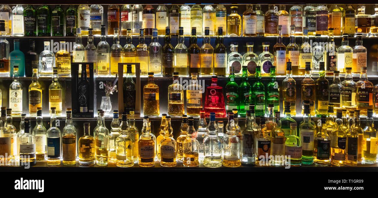 Una amplia selección de whiskys escoceses iluminado en estantes de vidrio y en óptica, Escocia Imagen De Stock