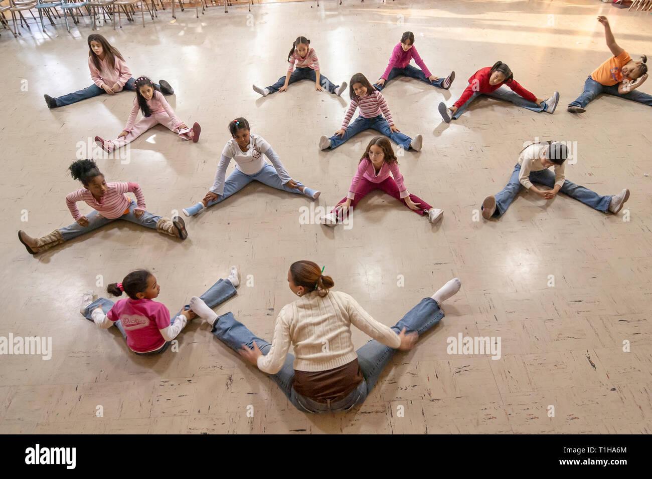 Los escolares sentados en el gimnasio haciendo ejercicio ejercicios con el instructor. Imagen De Stock