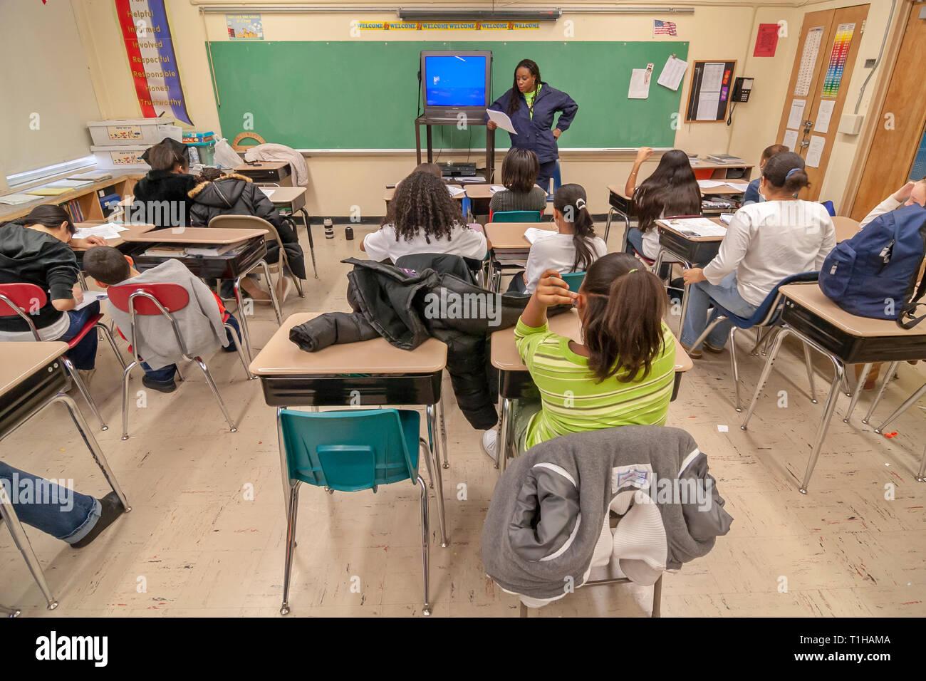 La escuela niños sentados en sus pupitres en un aula mientras el maestro les enseña. Imagen De Stock
