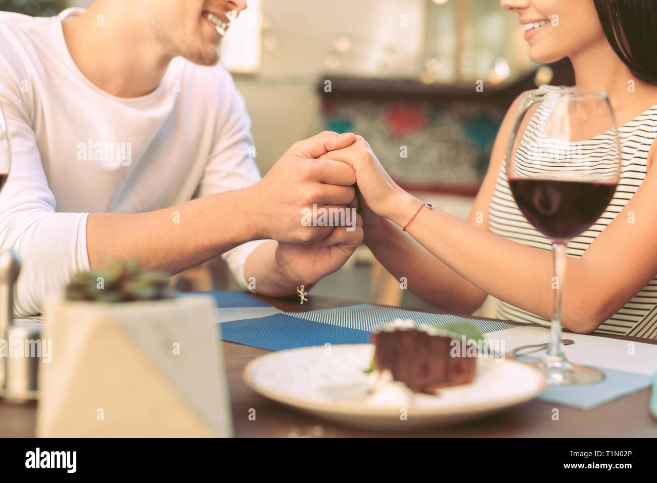 Adorable hombre sentimental sostiene suavemente las manos de su novia Foto de stock
