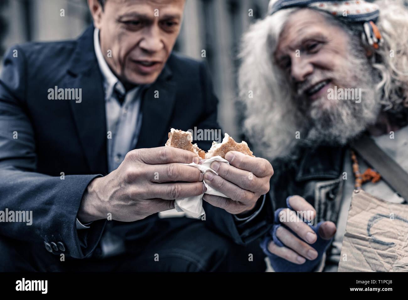 Tipo de hombre sincero en traje de oficina compartir sandwich con hombre sin hogar Imagen De Stock