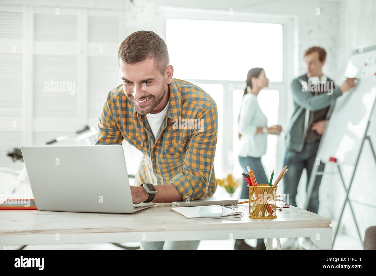 Smart hombre positivo escribiendo en su portátil. Foto de stock