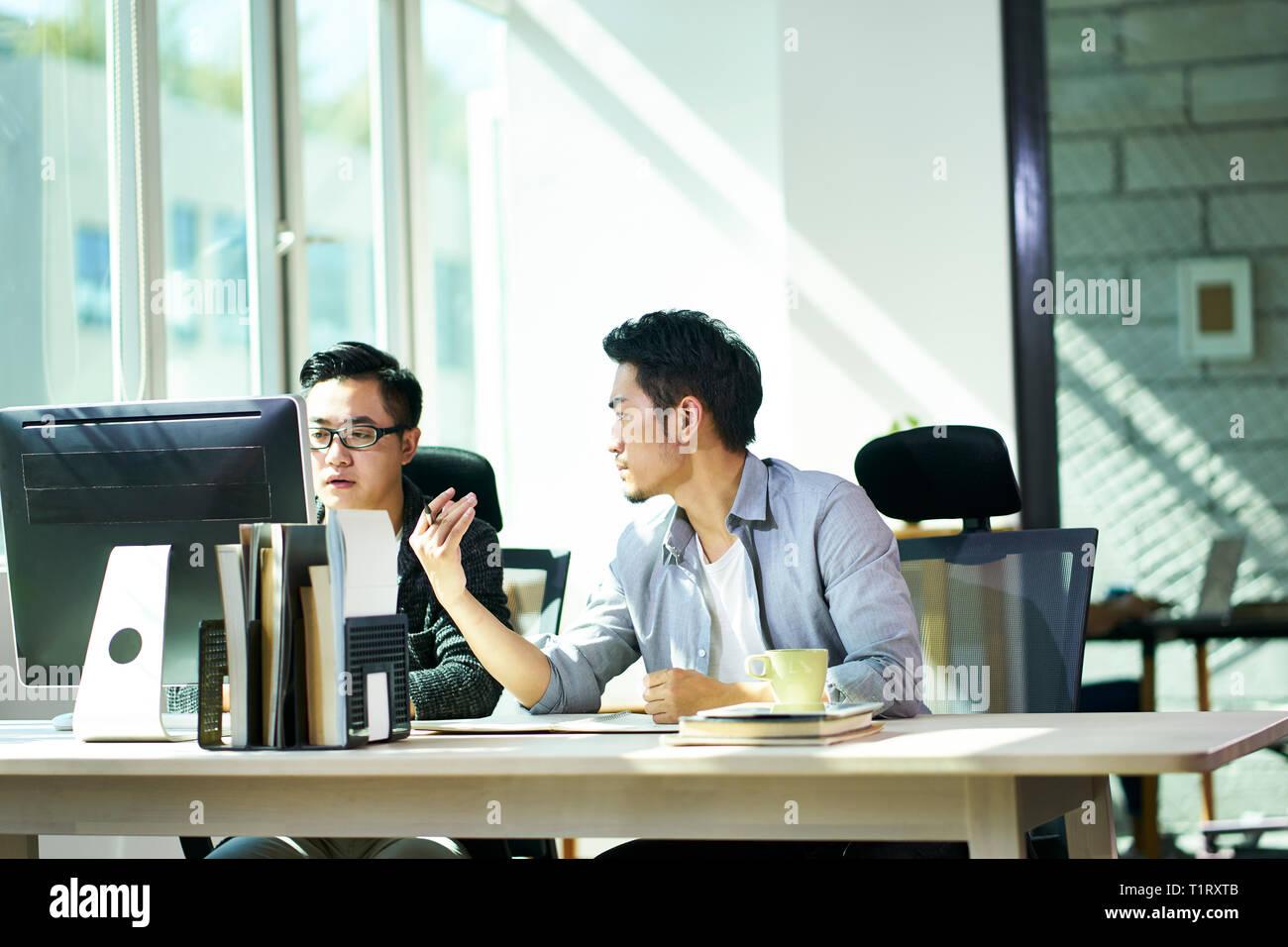 Dos jóvenes empresarios asiáticos trabajan juntos en la oficina hablando de negocios. Foto de stock