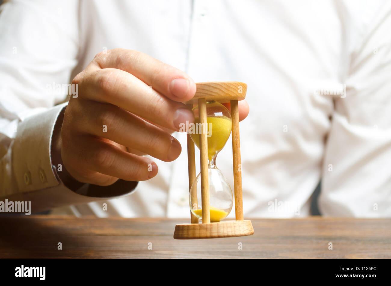 Reloj de arena en las manos de una persona en una camisa blanca. La gestión de la empresa. Gestión del tiempo aumenta la eficiencia, reduce los costos y la burocracia. Logística Foto de stock