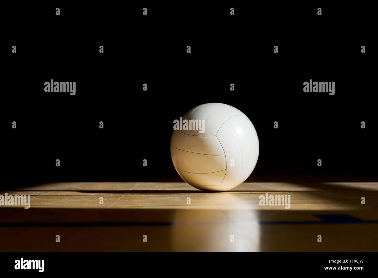 Cancha de voleibol con piso de madera aislado sobre la bola negra con espacio de copia Imagen De Stock