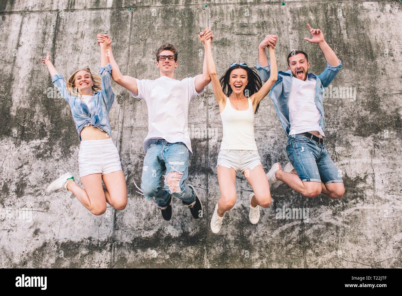 Impresionante y gente agradable están saltando en el aire. Están manteniendo sus manos en el aire. Empresa es en el fondo gris. Son positiv Imagen De Stock