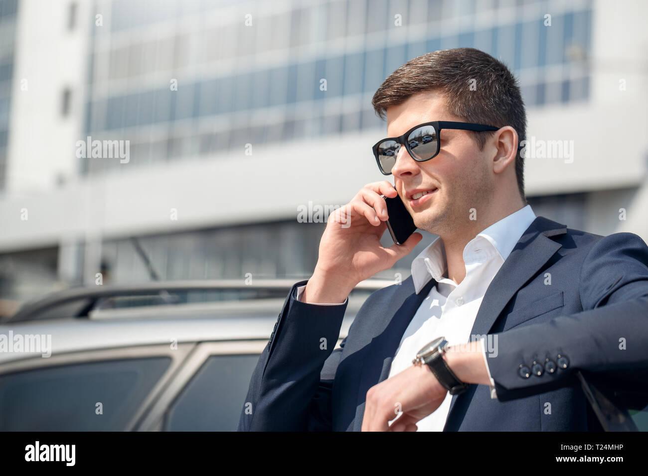 73374077f4 Empresario joven con gafas de sol de pie apoyándose en coche hablando en  smartphone con un