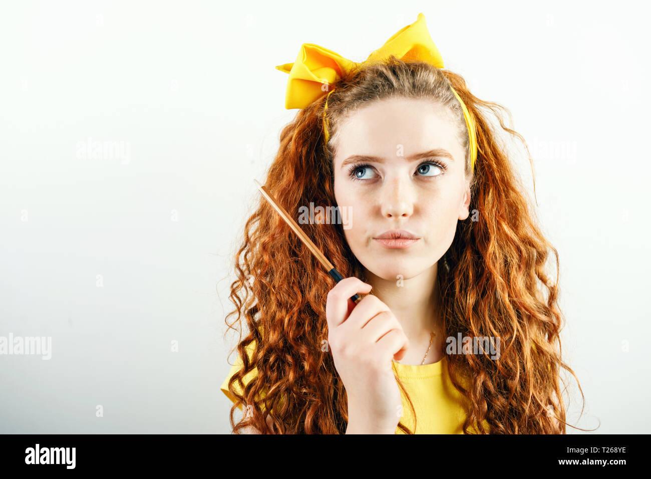 Pensativo curly jengibre amarillo chica con un arco sobre su cabeza la celebración de lápiz y pensando en algo mientras está parado sobre el fondo blanco. Foto de stock