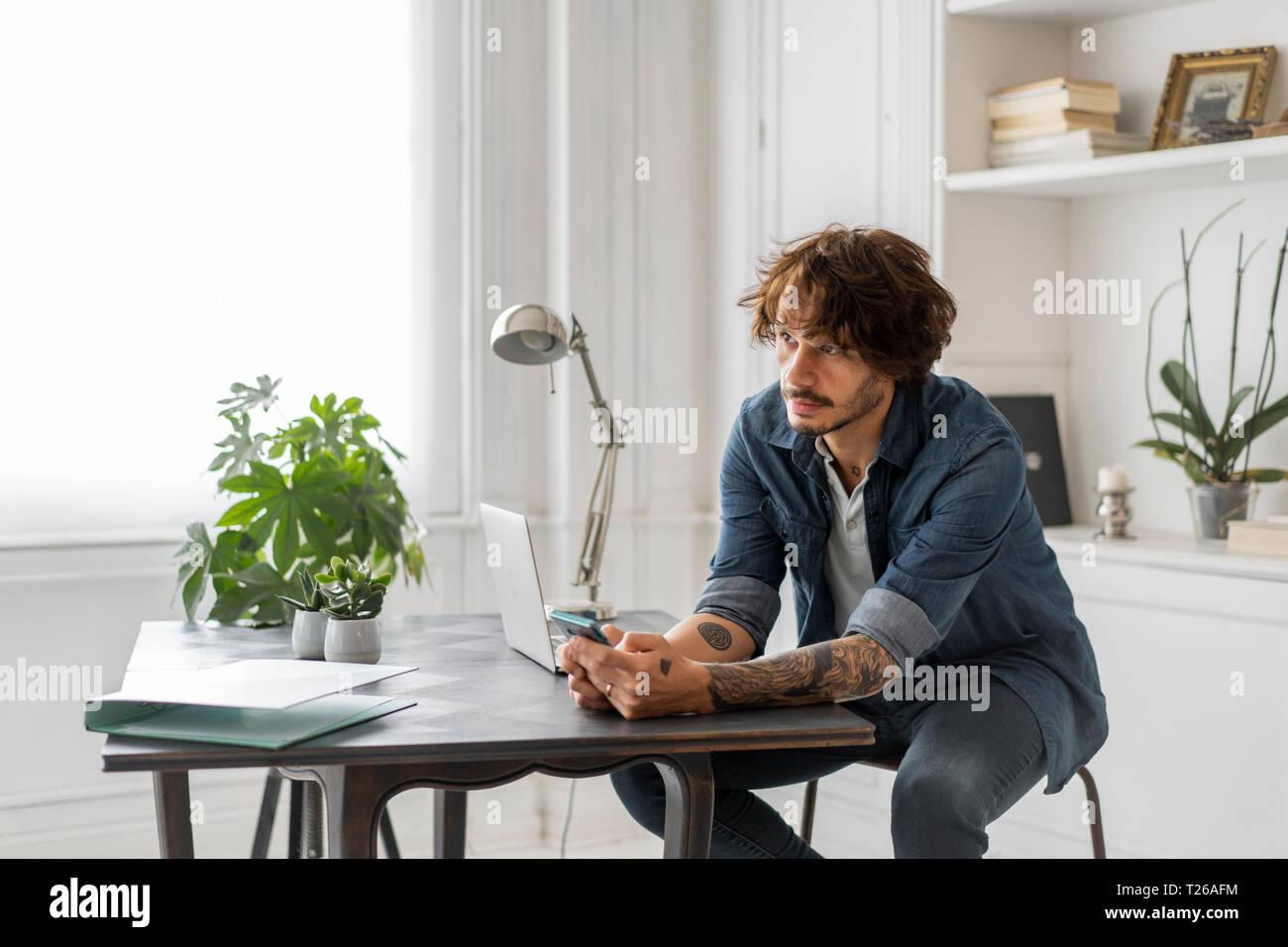 Hombre trabajando en espacio de coworking, usando smartphone, pensando Foto de stock
