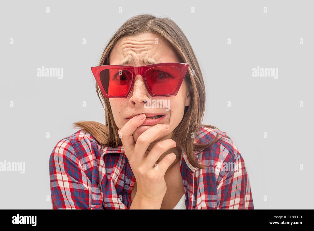 53eba61a0280 Preocupado e infeliz mujer joven mira a la cámara a través de gafas rojas.  Ella