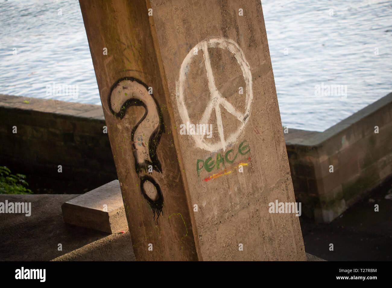 Graffiti en el puente admite - signo de interrogación y la paz internacional, símbolo de la paz la CND. Imagen De Stock