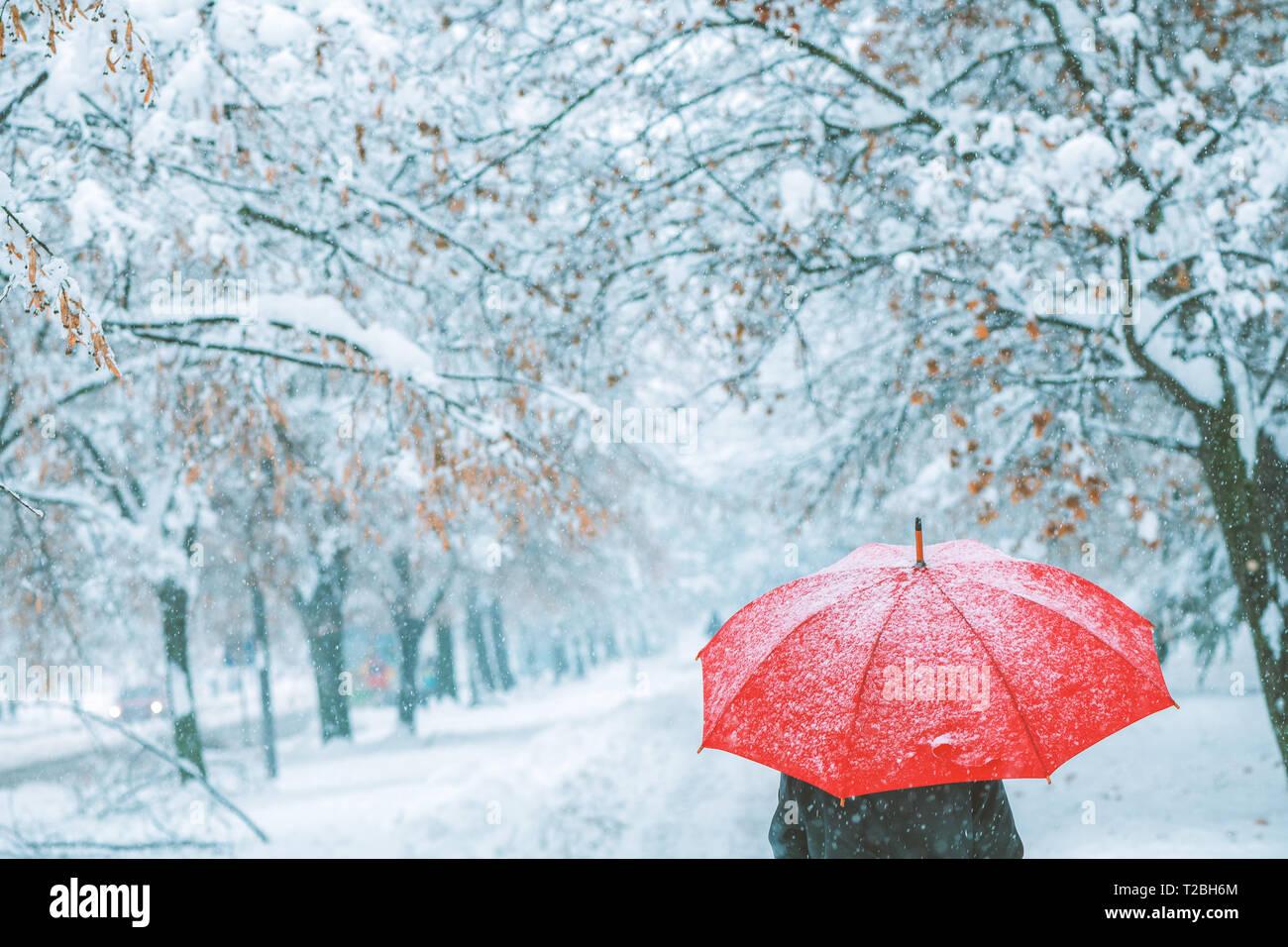 Mujer bajo la sombrilla roja en la nieve disfrutando de la primera nevada de la temporada de invierno Imagen De Stock