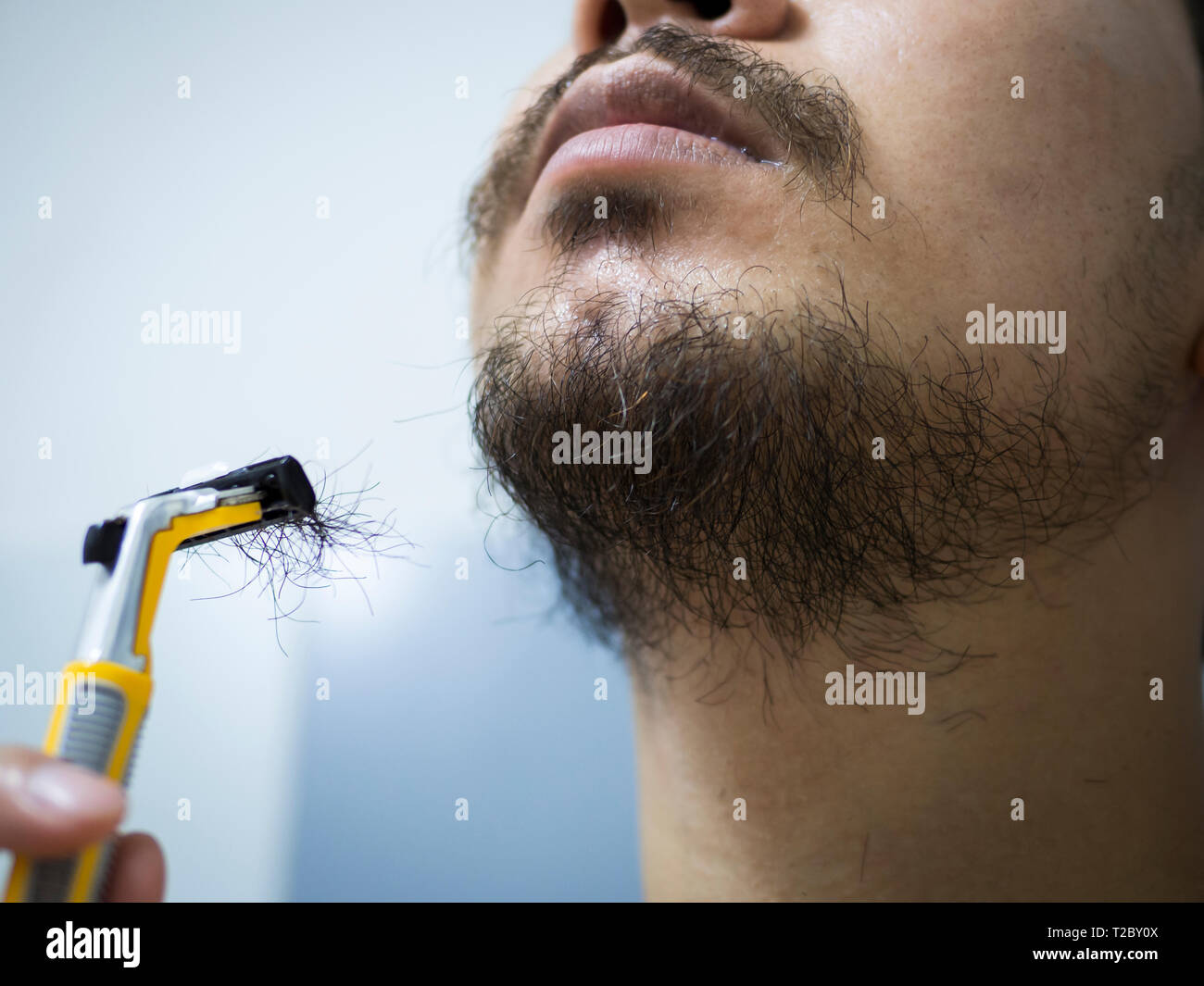 Closeup hombre utilice el amarillo afeitadora desordenado de afeitado de la barba y el bigote en su rostro en el baño. Foto de stock