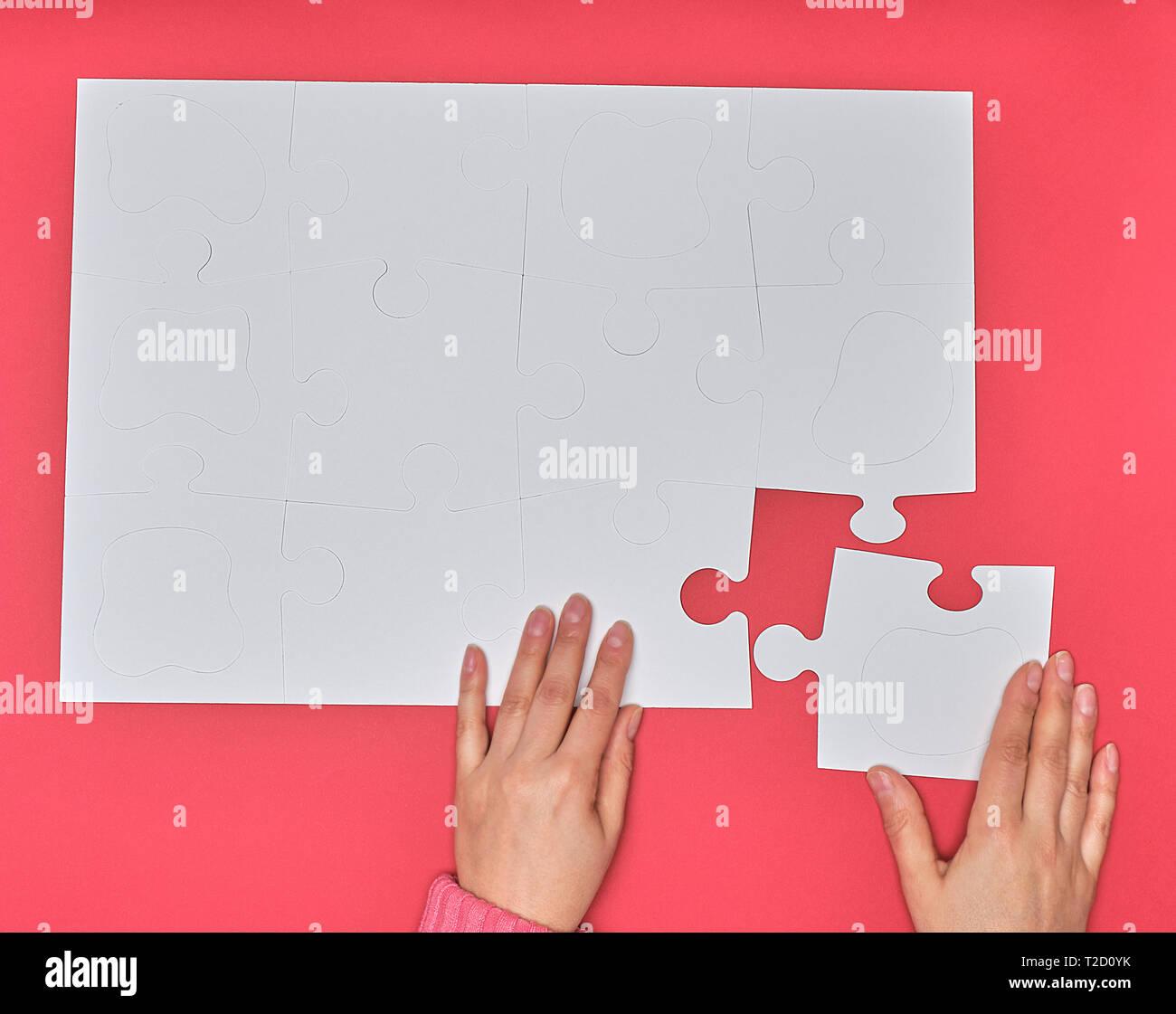 Mano femenina pone grande blanca puzzles en un fondo de color rosa, uno de los elementos que faltaban, vista superior Foto de stock