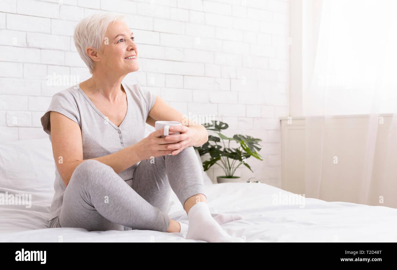 Disfrutar cada día de la vida. Encantado altos mujer relajante en la cama con una taza de té caliente, panorama con espacio libre Imagen De Stock