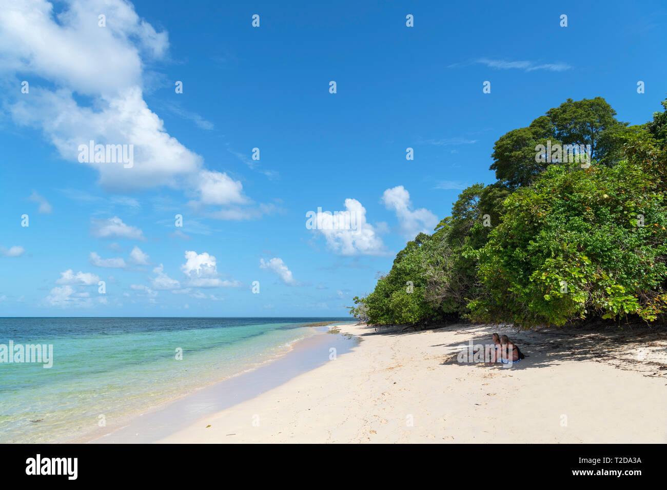 La Gran Barrera de Coral de Australia. Pareja Sentada en la playa en Isla Verde, un coral cay en el Parque Marino de la Gran Barrera de Coral, Queensland, Australia Foto de stock
