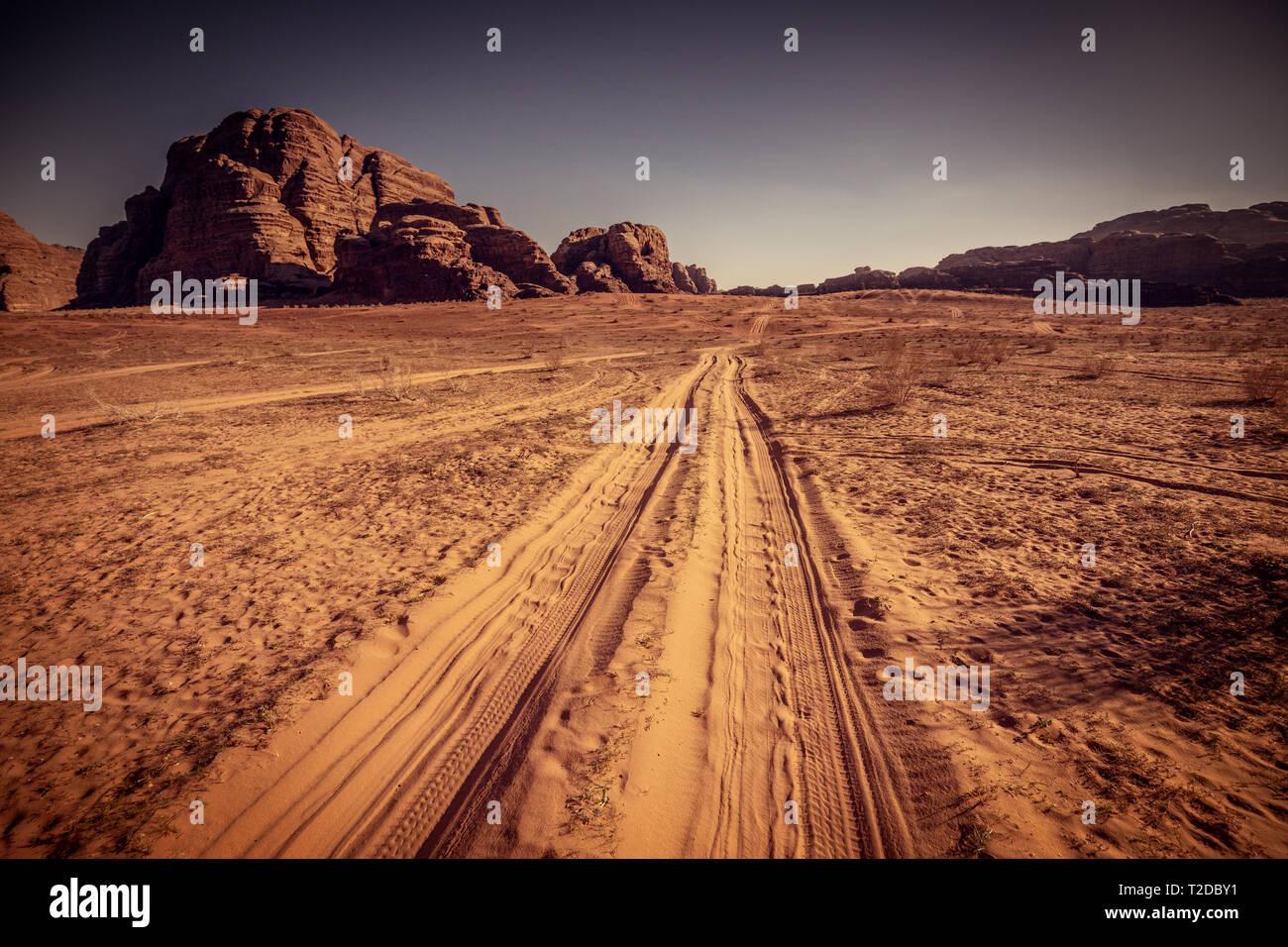 Sugestivas vistas del desierto de Wadi Rum en Jordania, el detalle de las huellas dejadas por los numerosos vehículos todoterreno que recorren una ruta turística cada día. Imagen De Stock