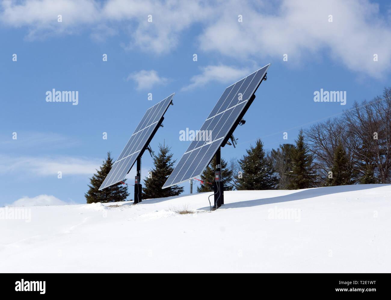 Free Standing montados en postes de los paneles solares fotovoltaicos residenciales en lo alto de una colina en un entorno rural de invierno. Foto de stock