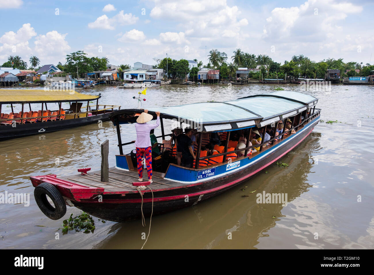 Los turistas en viaje en barco tradicional de río en el Delta del Mekong. Cai Be, Tien Giang, Viet Nam, Asia Imagen De Stock