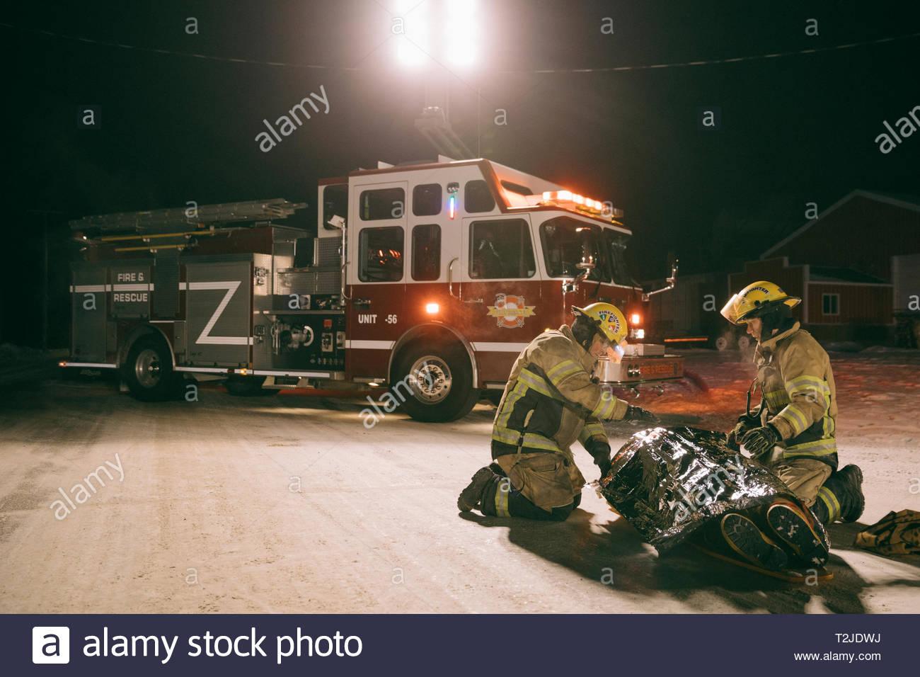 Los bomberos tendiendo a la víctima en la escena del accidente Imagen De Stock