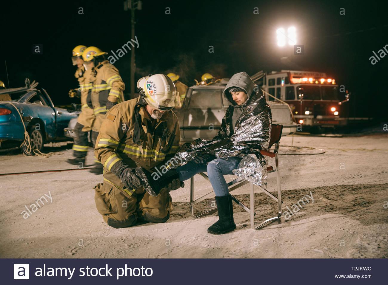 El bombero tendiendo a víctima de accidente de coche Imagen De Stock