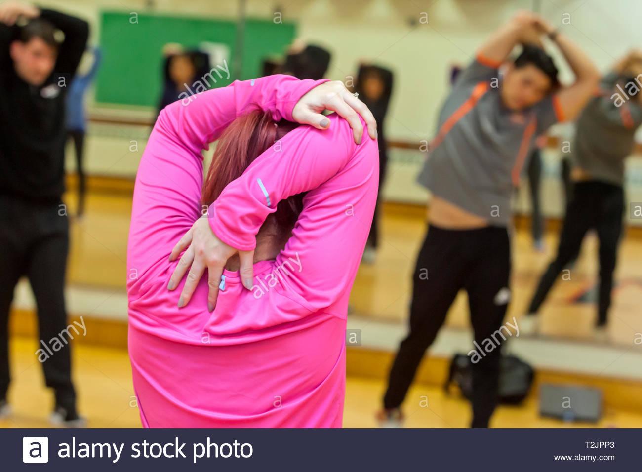 Hombres y mujeres en una clase de ejercicios en un gimnasio. Imagen De Stock
