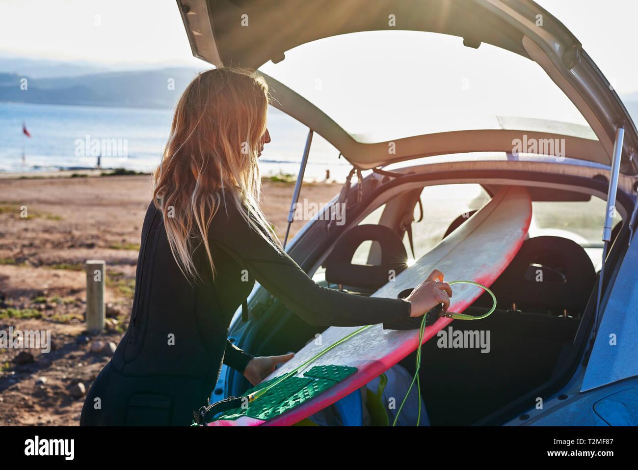 Mujer joven quitando tablas de surf desde el maletero del coche Foto de stock