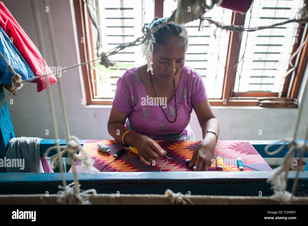 Una mujer nepalesa bordar seda y pashmina chales de lana de telar, en W.F. Nepal, una ONG que emplean mujeres marginalizadas sobre una base de igualdad de derechos. Imagen De Stock