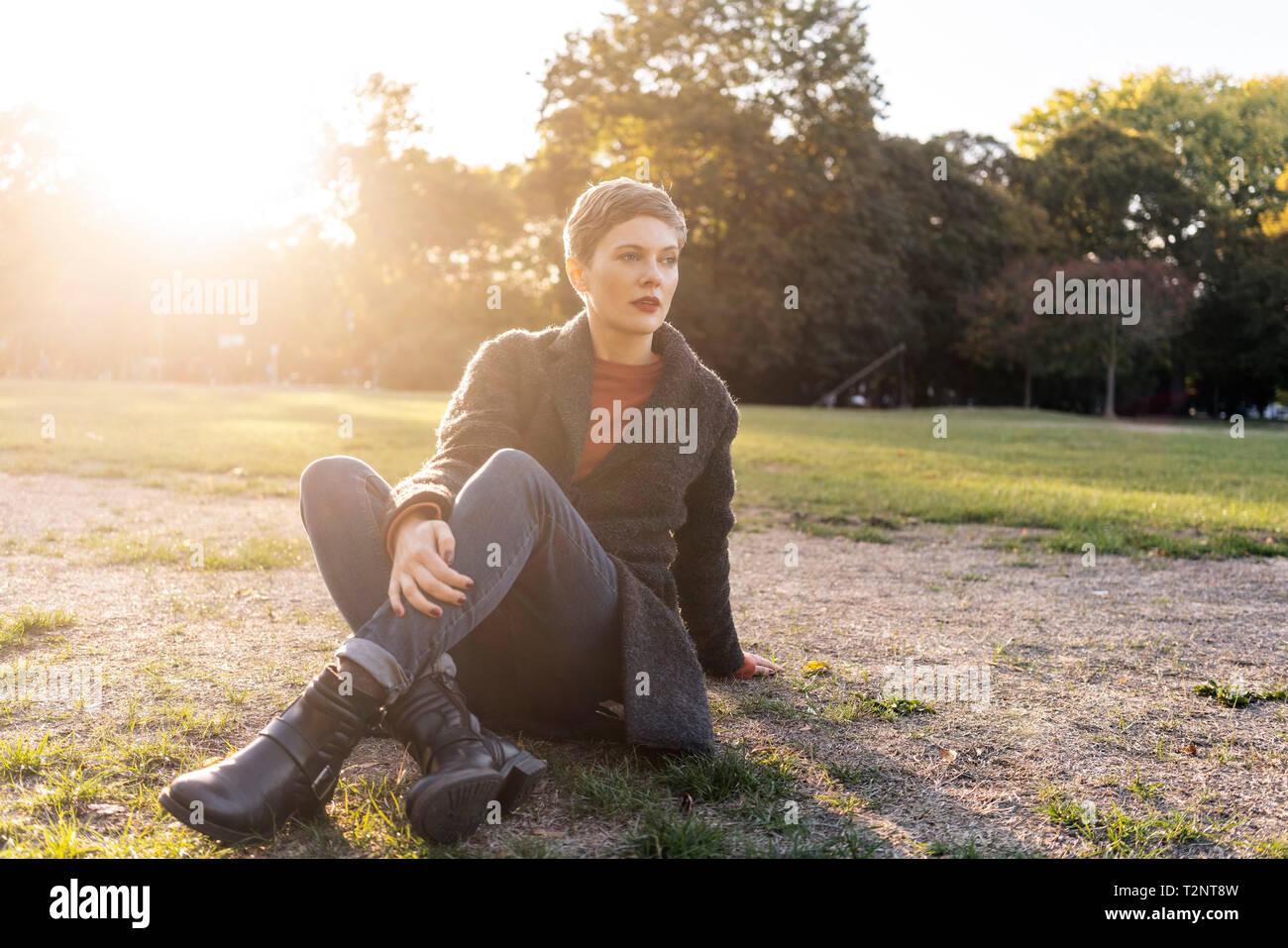 La mujer disfruta de sol en park Foto de stock