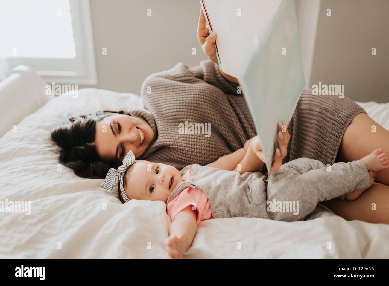 Madre leyendo con el bebé en la cama en el dormitorio Foto de stock