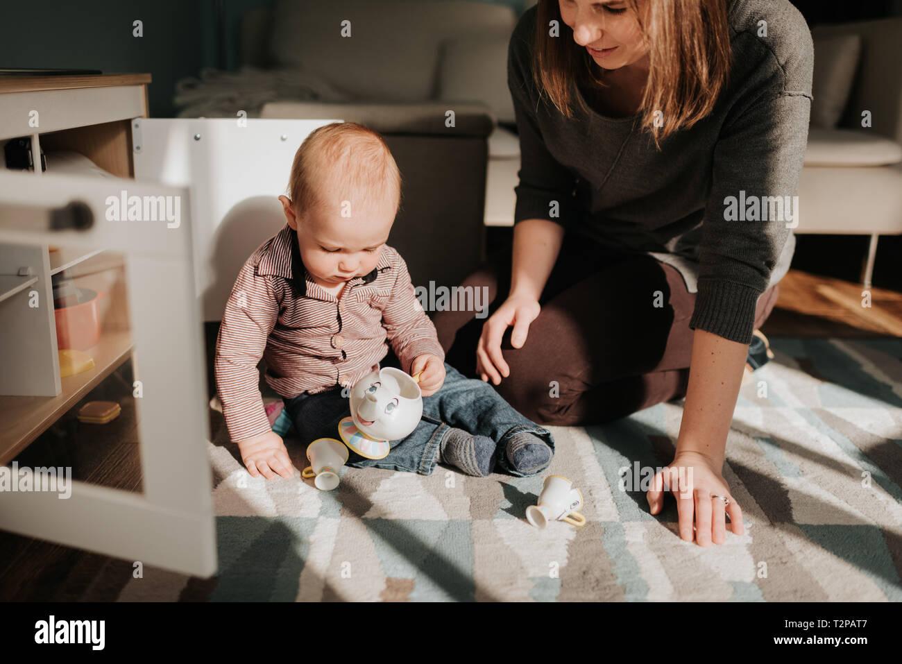 Madre jugando con su hijo en el salón alfombra Foto de stock