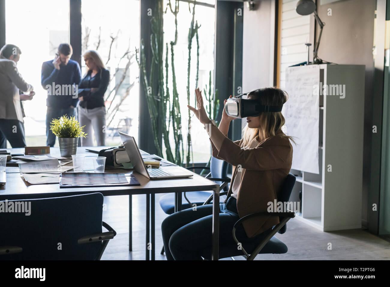 La empresaria con casco de realidad virtual en una oficina, colegas en segundo plano. Foto de stock