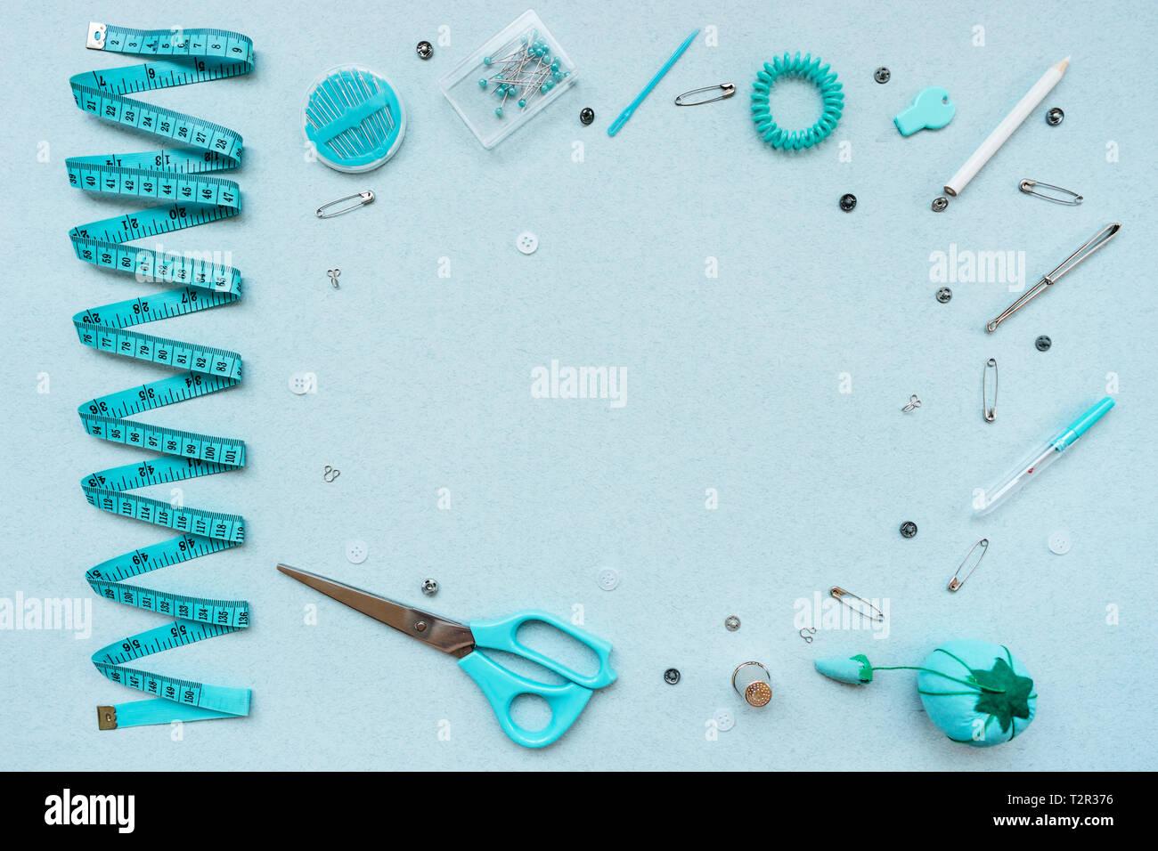 Kit de costura sobre un fondo azul. Cinta, tijeras, alfileres, agujas, botones, botones desgarrador dedal peso lápiz crayon vista desde arriba Foto de stock