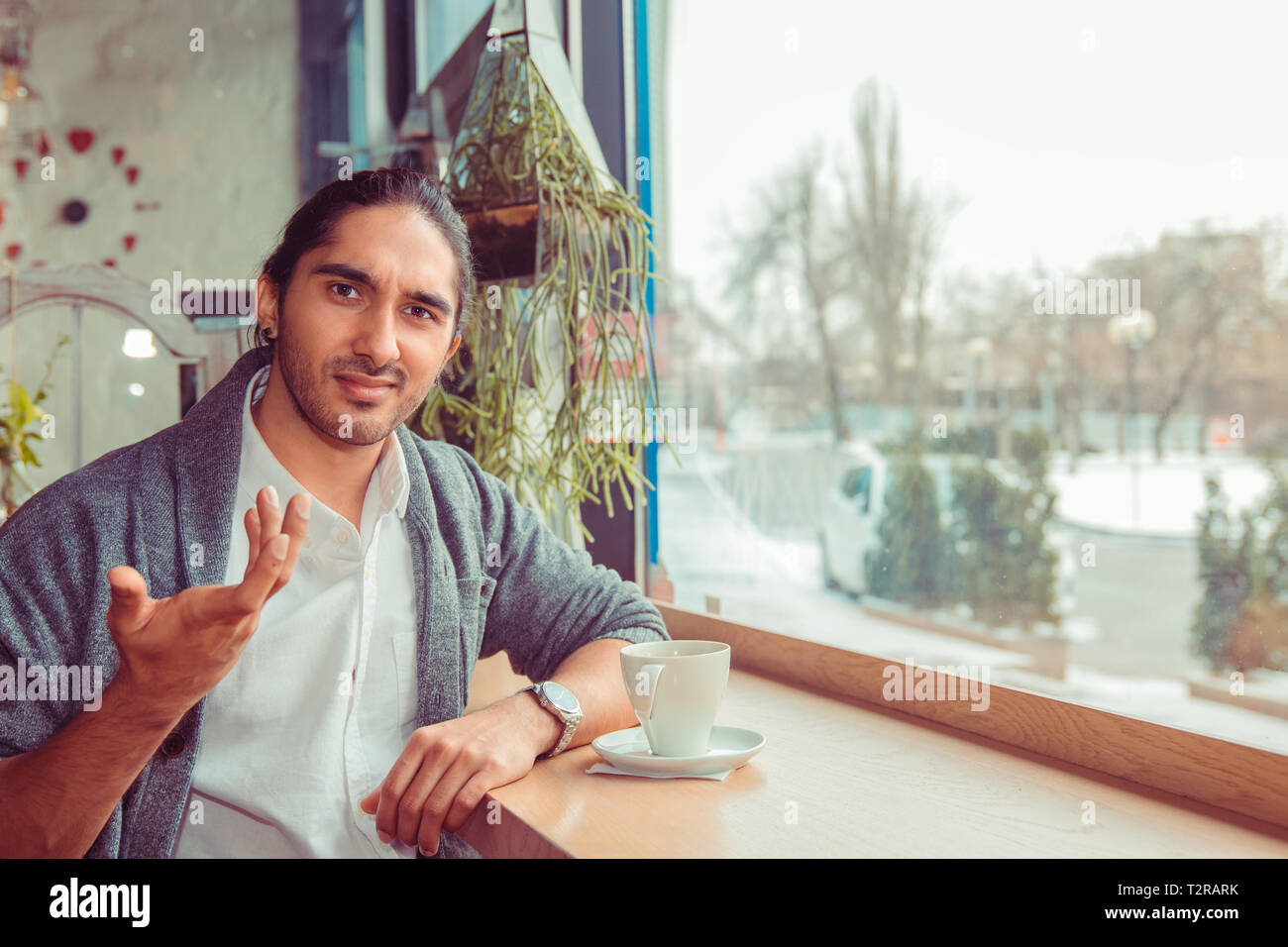Frustrado el hombre gesticula ¿qué quieres de mí, entonces, ¿qué, no sé. Closeup retrato de un guapo muchacho indio turco vistiendo la camiseta blanca, gris Imagen De Stock