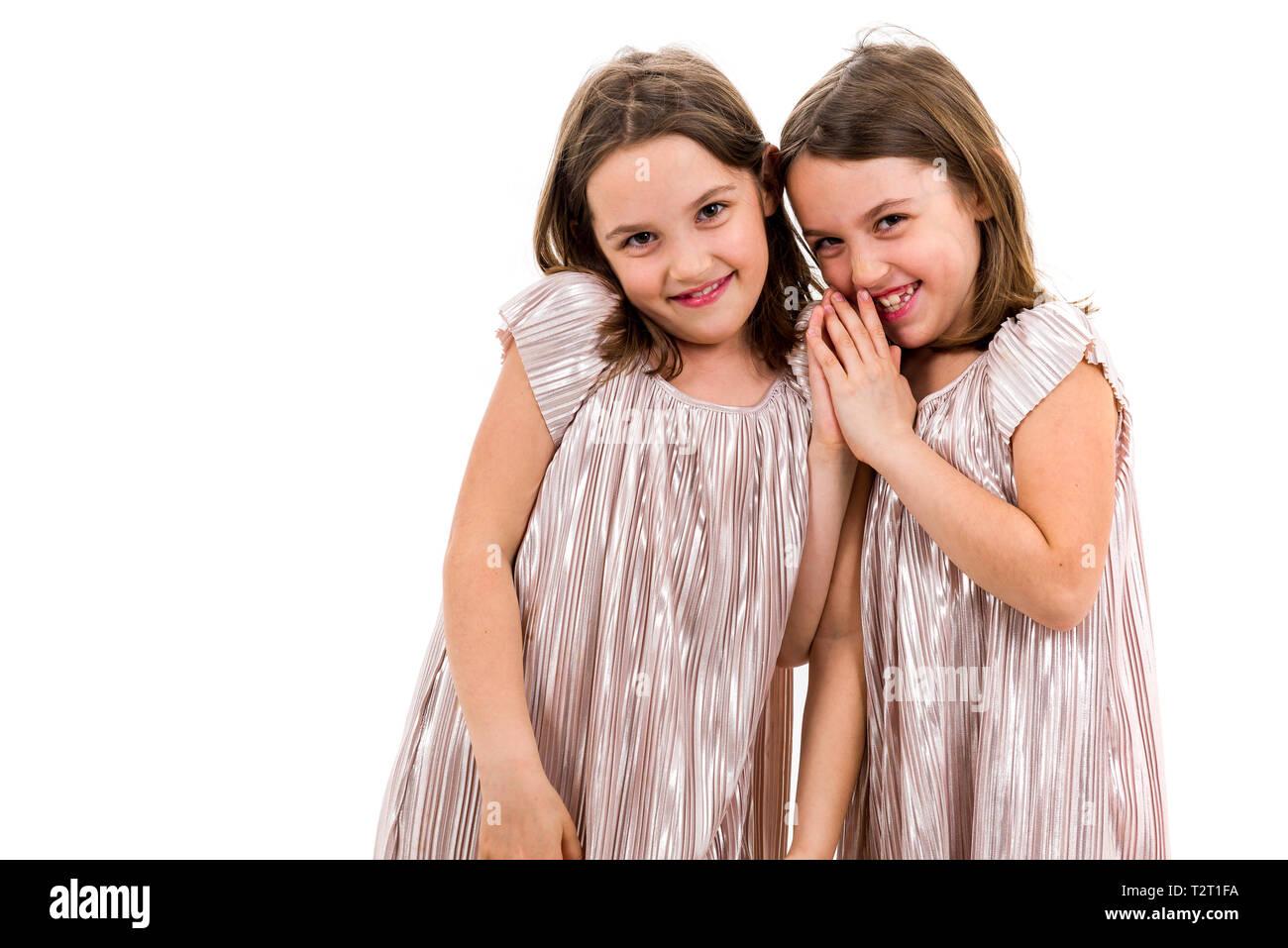 1a9b6c0e20 Dos gemelas hermanas están posando para la cámara. Feliz hermanas gemelas  en vestidos están mirando