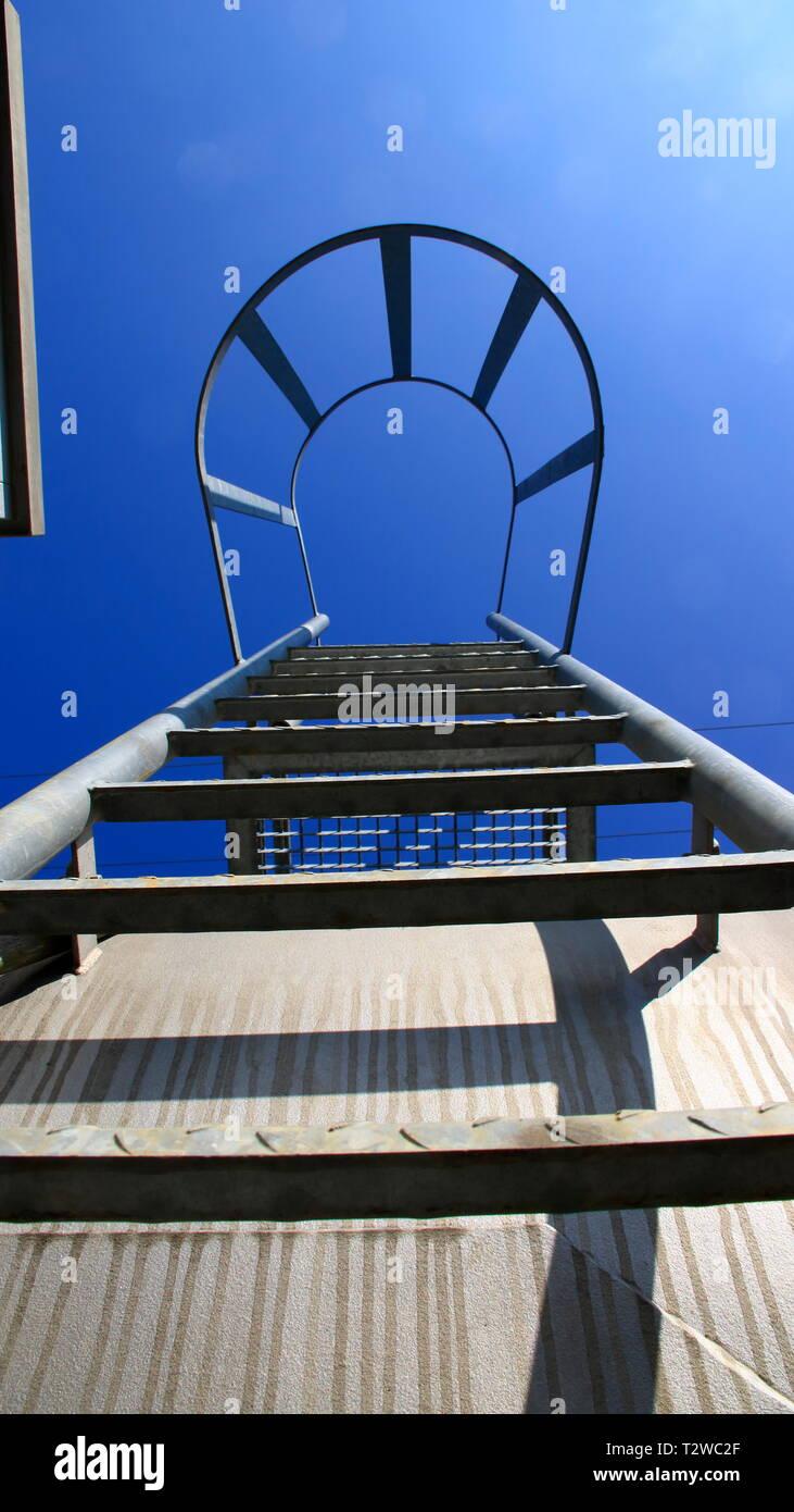 Vista desde debajo de una escalera con barra de seguridad. El aspecto simboliza el ascenso con certeza. Imagen De Stock