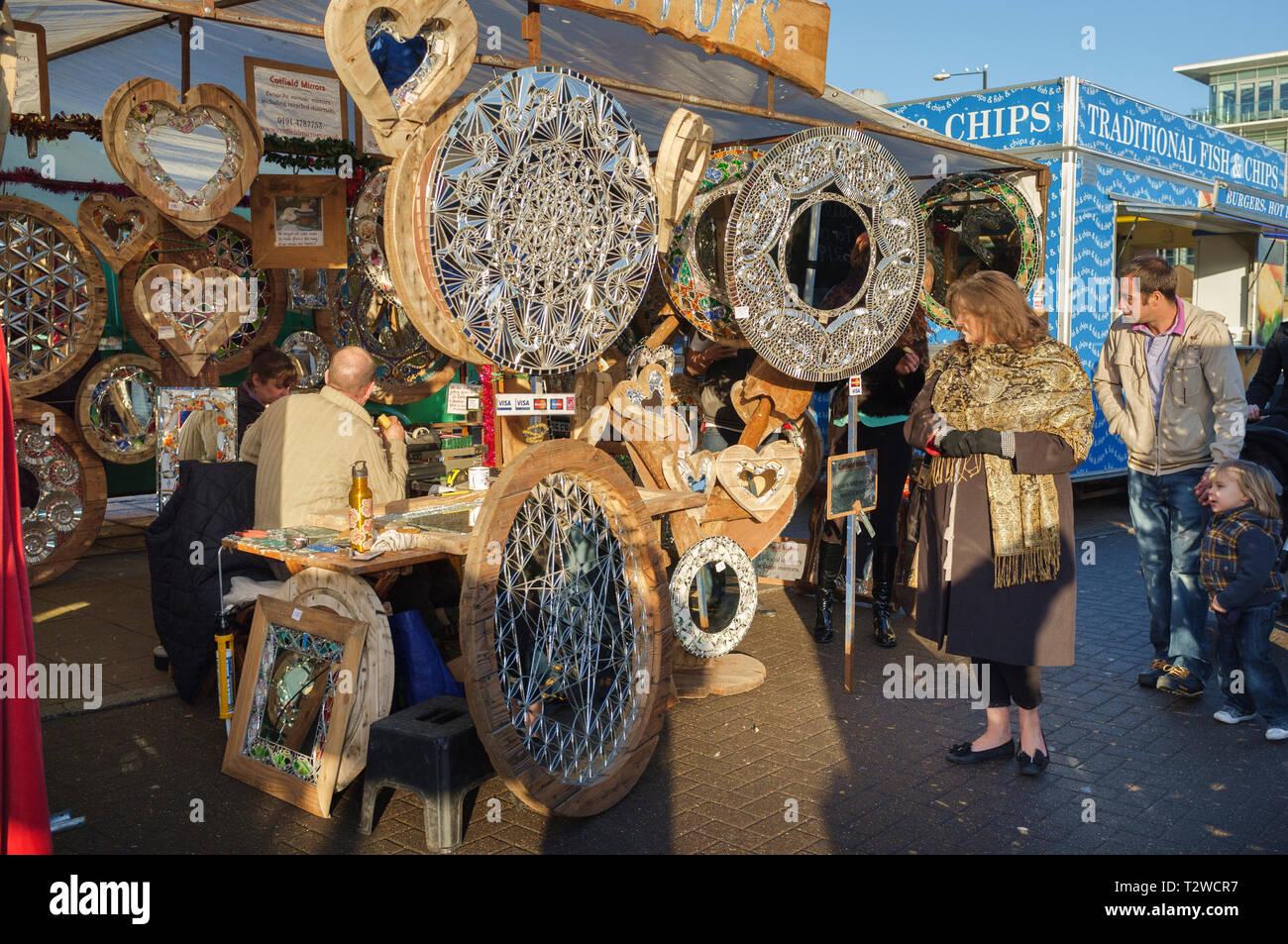 Los compradores de vidrio y espejos decorativos de visualización en venta a un puesto en el mercado en el Quayside mercado dominical en Newcastle upon Tyne Imagen De Stock