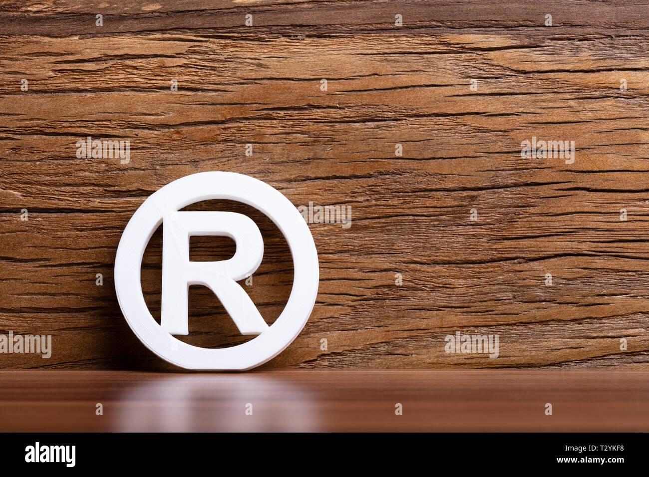 Signo de marca registrada en frente de la pared de madera Foto de stock