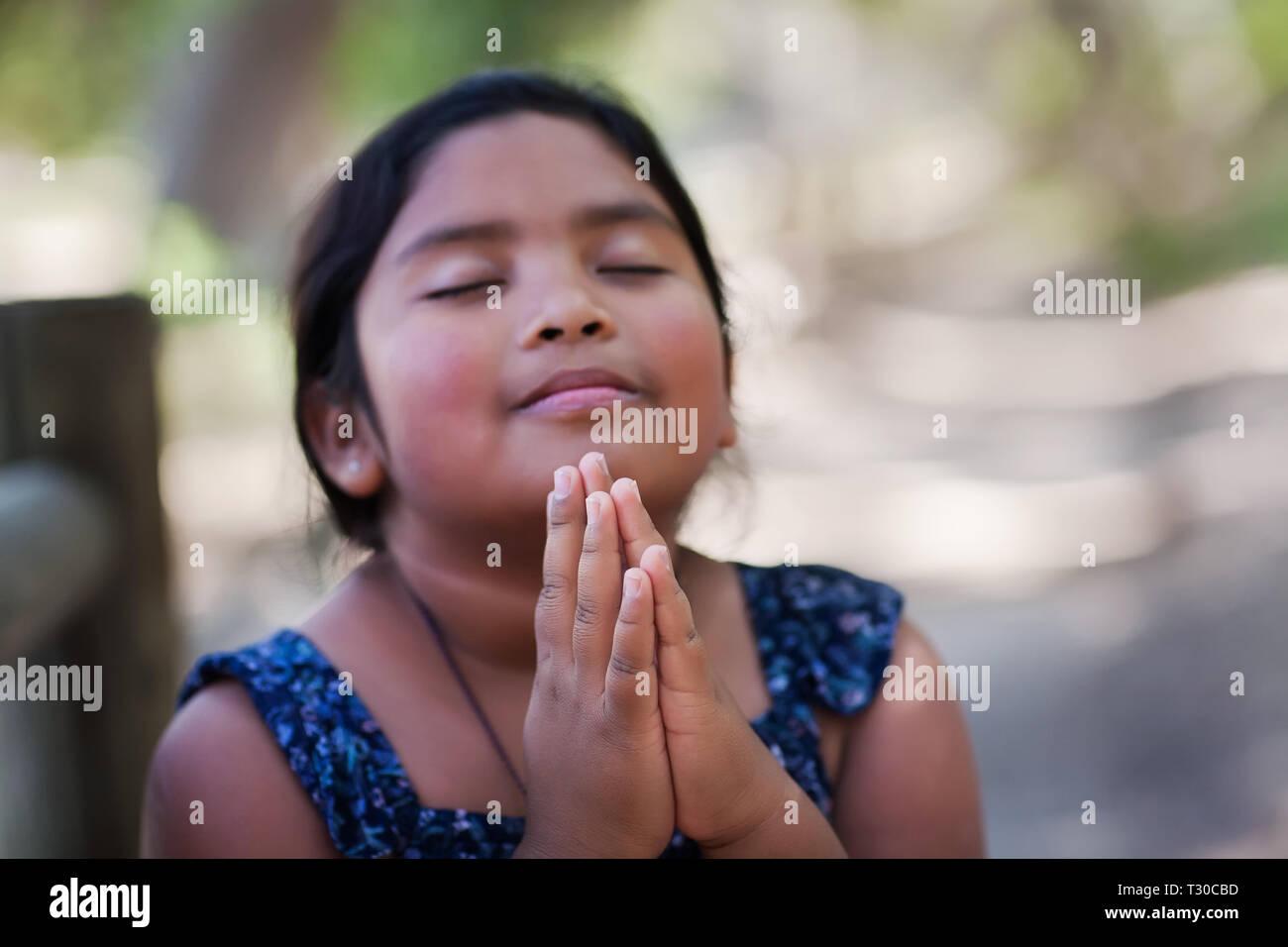 Una chica joven nativa con las manos juntas en oración, en un escenario al aire libre en oración a Dios con una sonrisa sutil. Imagen De Stock