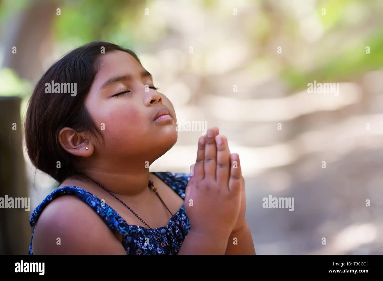Una niña rezando con las manos juntas en la reverencia a Dios, vistiendo ropa conservadora y en un escenario al aire libre. Imagen De Stock